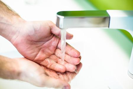 Washing hand under tap water