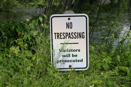 Sign No Tresspassing - covered with overgrown grass Stock Photo