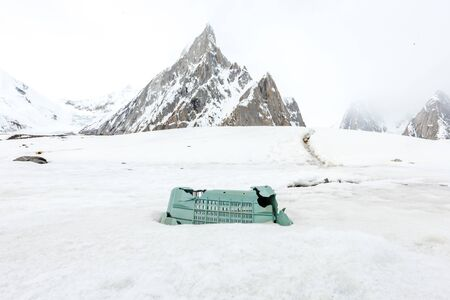 Garbage scattered over snowy mountain. Let's save the planet and recycle the excess garbage. Pollution Concept 免版税图像