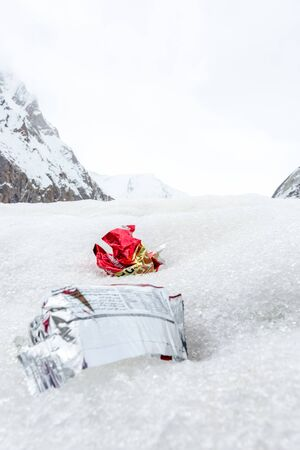 Garbage scattered over snowy mountain. Let's save the planet and recycle the excess garbage. Pollution Concept Stock Photo