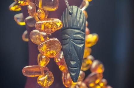 maschera tribale: African maschera tribale con una collana di ambra sullo sfondo scuro.
