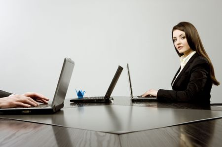 Beautiful young businesswoman sitting at a desk with three laptops with blue origami on one of them and human hands on another one photo