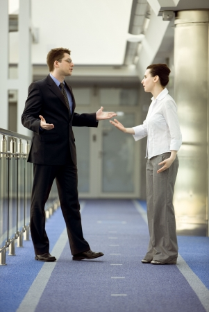 Businessman and businesswoman having argument in modern office corridor