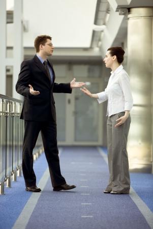 argument: Zakenman en zakenvrouw die redenering in het moderne kantoor-corridor
