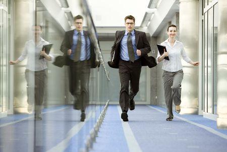Businessman and businesswoman running on modern office corridor.