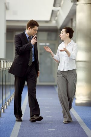gesticulation: Businessman and businesswoman walking and talking on modern office building corridor.