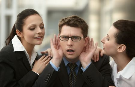 Businessman listening to advice from two woman whispering to ear in the office