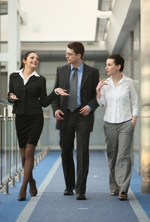Business portrait of tree presons - young man and two women walking and talking on modern office corridor