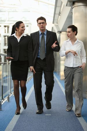 discuss: Business portrait of tree presons - young man and two women walking and talking on modern office corridor