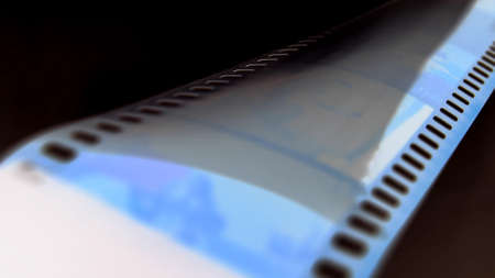 Watching Retro Pictures on Negative Plastic Film Strip Roll