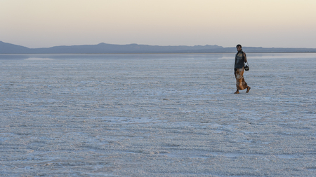 Afar soldier walking during sunset on the salt plains of Asale Lake in the Danakil Depression in Ethiopia, Africa
