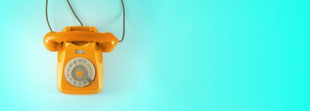 Orange vintage dial telephone with blue background.