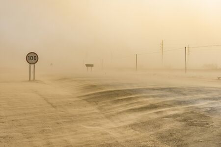 Sandstorm covering the road from Swakopmund to Walvis Bay in Namibia in Africa.