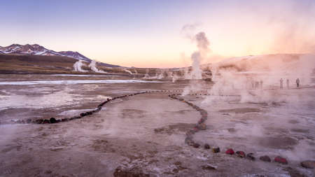 Sunrise at Geyser El Tatio near San Pedro de Atacama in Chile. Landscape with gas smoking and people in backlight.