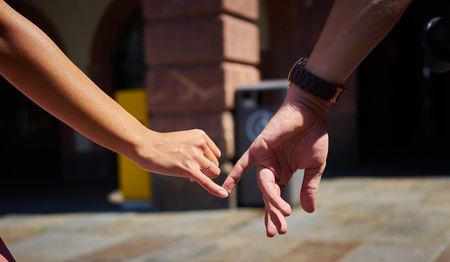 girl with a wristwatch: Engaged couple walking in city and holding hands Boy and girl holding hands with engagement ring Lovers shopping in the city Stock Photo