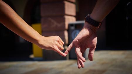 dedo meÑique: pareja comprometida que recorre en ciudad y de la mano niño y niña de la mano con los amantes del anillo de compromiso de compras por la ciudad Foto de archivo
