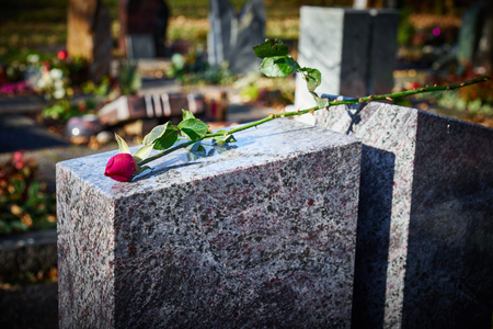 Gravestone with withered rose Tomb stone on graveyard Sorrow about loss of beloved ones