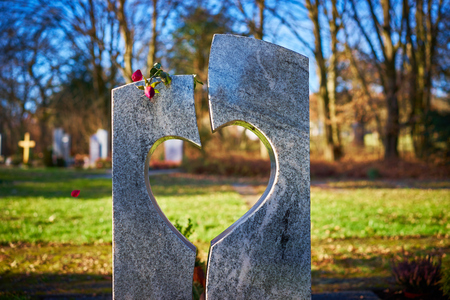 Grave stone with heart withered rose Tomb stone with heart on graveyard Sorrow about loss of beloved ones