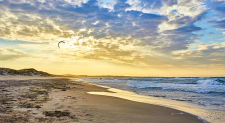 kiter: Kitesurfing on ocean at sunset in sardinia