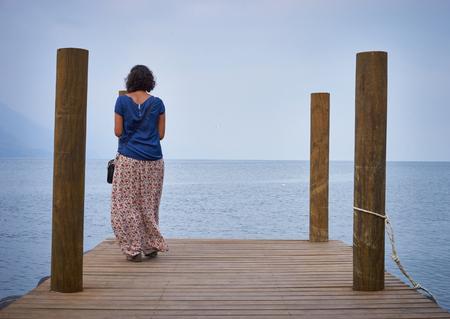 mujer mirando el horizonte: Mujer solitaria mirando el horizonte de niebla Foto de archivo