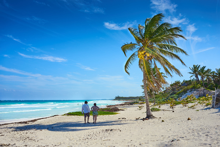 Couple at tropical beach of Tulum in Mexico  Untouched paradise under marvelous coconuttrees  Summer vacation in caribbeans Stock Photo
