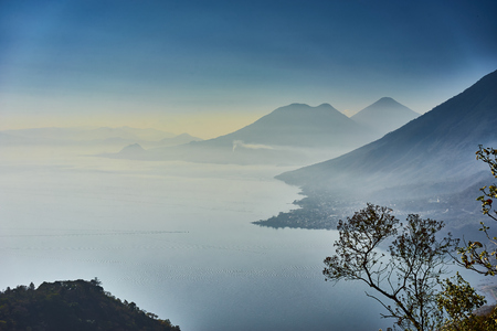 Foggy morning at lake in Guatemala in the morning hours  Highlands with volcanoes at Lake Atitlan in Guatemala  Famous tourist spot in Guatemala
