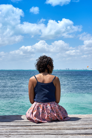 Lonesome woman sitting on pier Standard-Bild