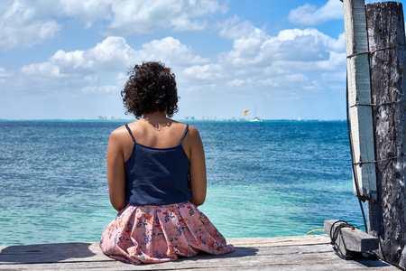 Lonesome woman sitting on pier  one woman looking at caribbean sea in Mexico Stock Photo