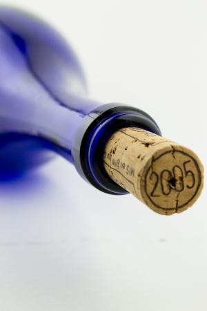 Wine in blue bottle isolated on white background photo