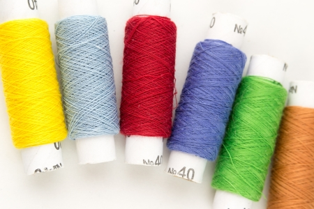 Many-coloured bobbins of thread closeup photo
