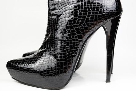 Black female crocodile boots isolated on white photo