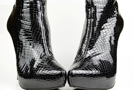 Black female crocodile boots isolated on white photo