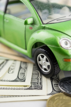 Toy car and money over white  Rent, buy or insurance car concept photo