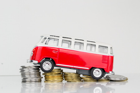 Toy car, key and money over white. Rent, buy or insurance car concept photo