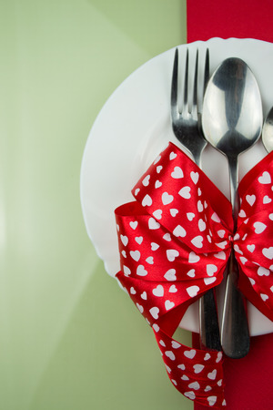Valentines day table setting with plate, fork, red ribbon and hearts photo