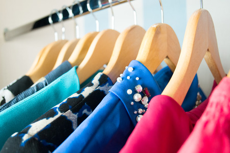 casual clothing: Different clothes on hangers close up