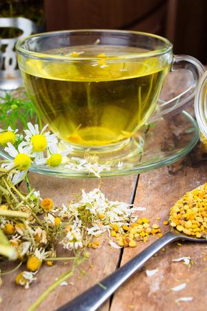 chamomile tea: Cup of chamomile tea with dry chamomile flowers