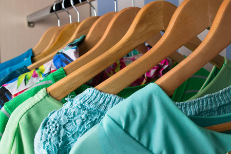 hangers: Colored female clothes on hangers in wardrobe