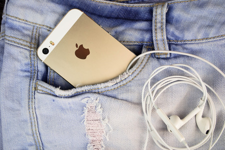 Apple Gold iPhone 5s in a blue denim pocket and iPhone earphones, close up