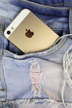 5s: Apple Gold iPhone 5s in a blue denim pocket and iPhone earphones, close up