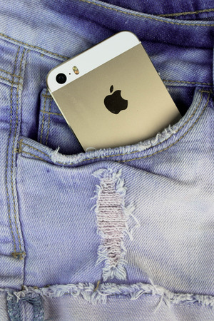 logo marketing: Apple Gold iPhone 5s in a blue denim pocket and iPhone earphones, close up