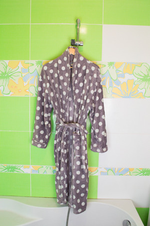 housecoat: Cream bathrobe on hanger with Lime green mosaic tiles background