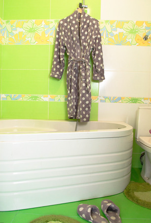 bath gown: Cream bathrobe on hanger with Lime green mosaic tiles background