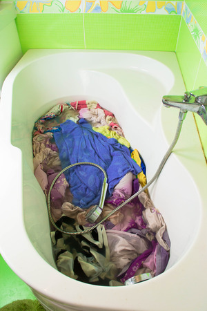 dirty clothes: Dirty clothes soak in tub with detergent before washing