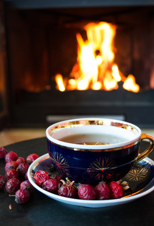 coffee mugs: Rosehip tea in front of roaring fire in a fire place