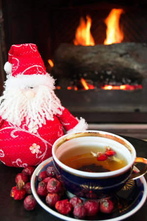 woodburning: Rosehip tea with snowman in front of roaring fire in a fire place
