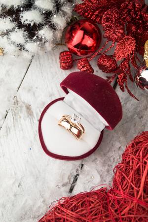 anillo de compromiso: Anillo de bodas entre decoraciones de Navidad en el fondo de madera.