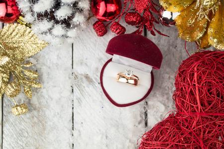 matrimonio feliz: Anillo de bodas entre decoraciones de Navidad en el fondo de madera.