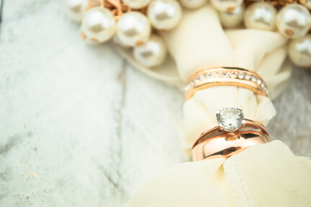 love gold: Golden wedding rings on white wood background