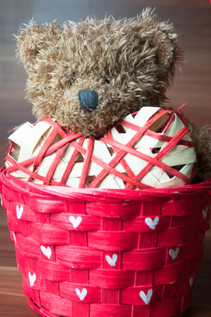 love hearts: Valentines teddy bear in the wicker basket on wooden background